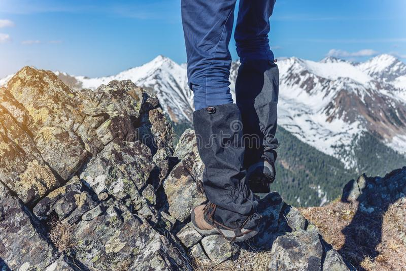 Man in Hiking boots stands on the rocks in front of the entrance to the peak on the background of the snowy mountains. A man in Hiking boots stands on the rocks stock images