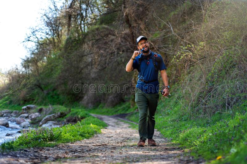 Man hiking and hydrating with water pipe royalty free stock photography