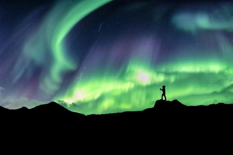 Man hiking on mountain with northern lights explosion. At norway royalty free stock photography