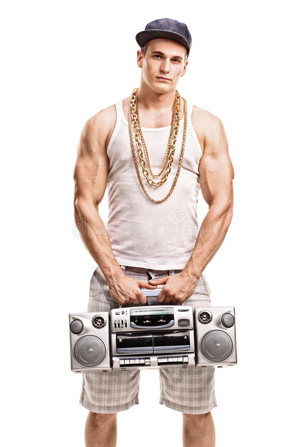Man in hip hop clothes holding a ghetto blaster. Vertical shot of a young muscular man in hip hop clothes holding a ghetto blaster and looking at the camera stock photo