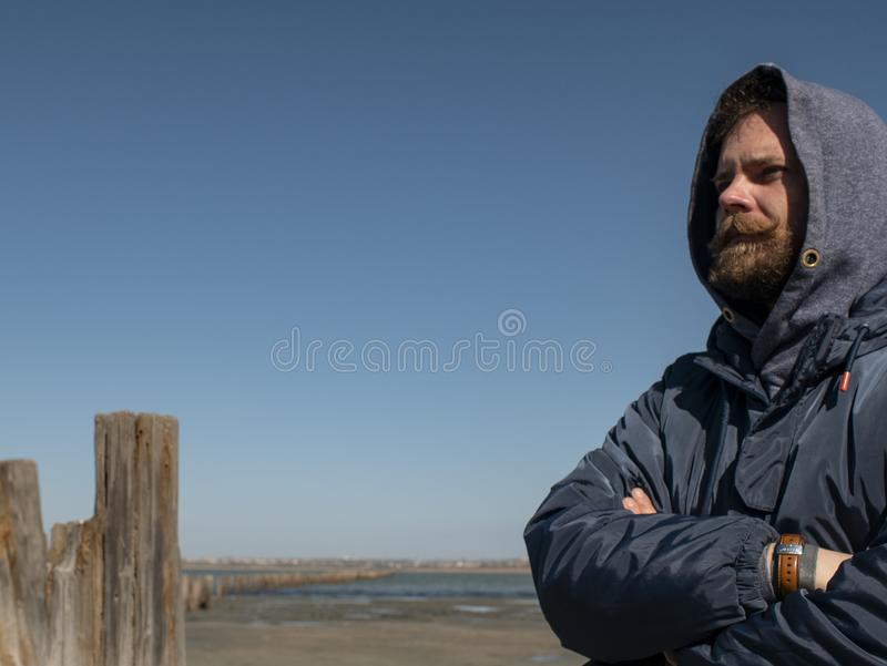 Man hipster with a beard and mustache in the hood against the blue sky and estuary royalty free stock photos