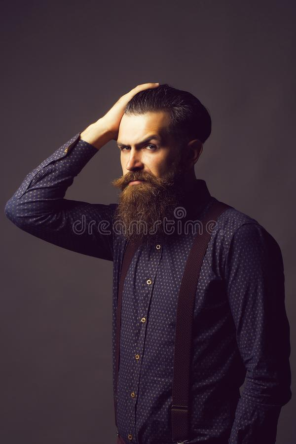 Man hipster tidies hair. Handsome man hipster with long graying brunette beard and moustache in shirt with suspenders tidies hair on grey background royalty free stock images