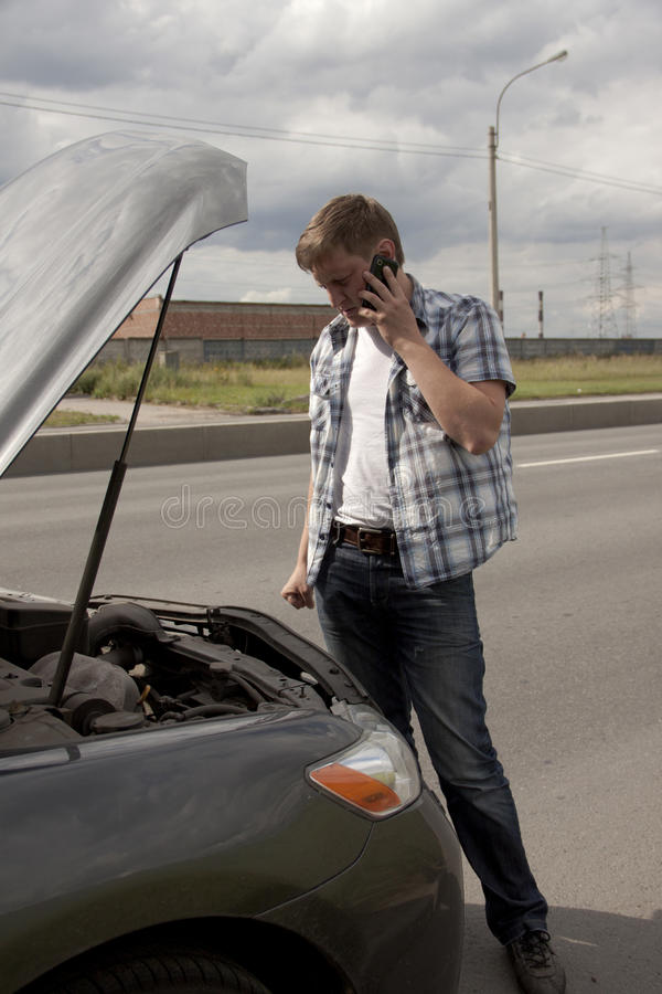 Man and his broken car. Man speaking on the phone beside his broken car royalty free stock photo
