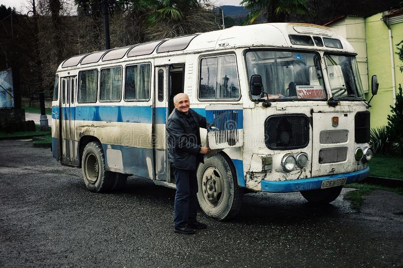 a man at his bus which is used as a camper van with his family opening the door royalty free stock photography