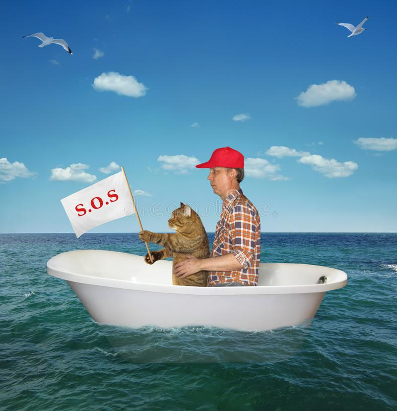 Man with his cat drift on the sea. The man in a red cap with his cat are drifting in a bathtub on the sea after a shipwreck. The cat holds a sign that says sos stock image