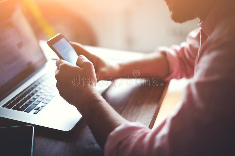 Man at his coworking place using technology, flare light stock photos