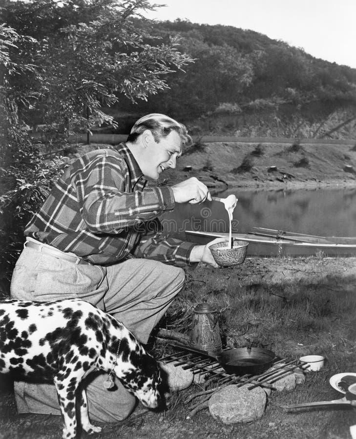 Man and his dog camping and preparing food stock photography