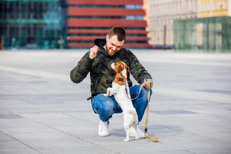 Man with his dog, Jack Russell Terrier, on the city street royalty free stock photo