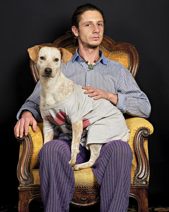 Portrait of a man and a dog. A man and his dog portrayed in the studio on an old armchair stock photos