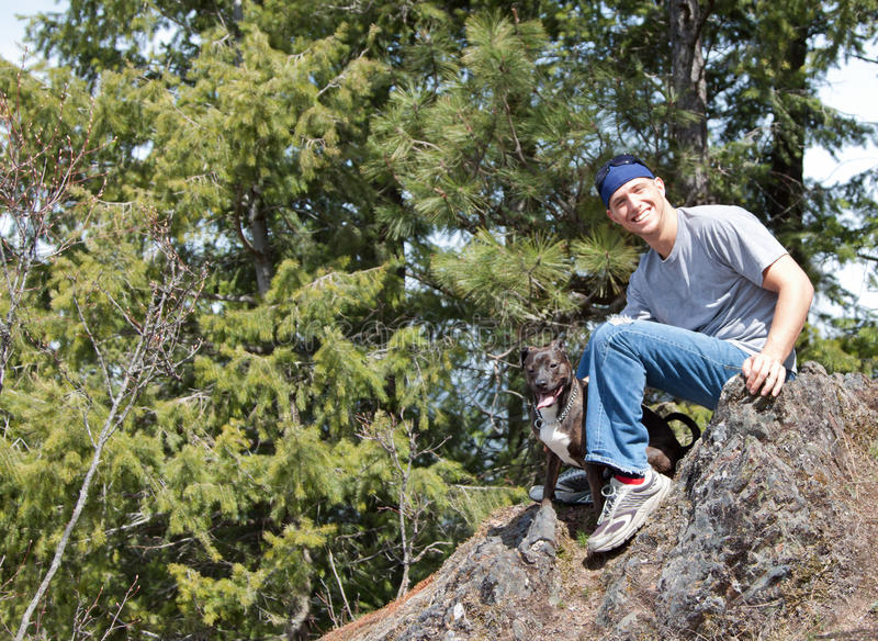 Download Man and his dog on a rock stock photo. Image of sitting - 24374870