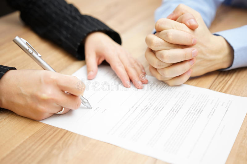 Man with his hands clasped is waiting woman to sign the contract.  stock photo