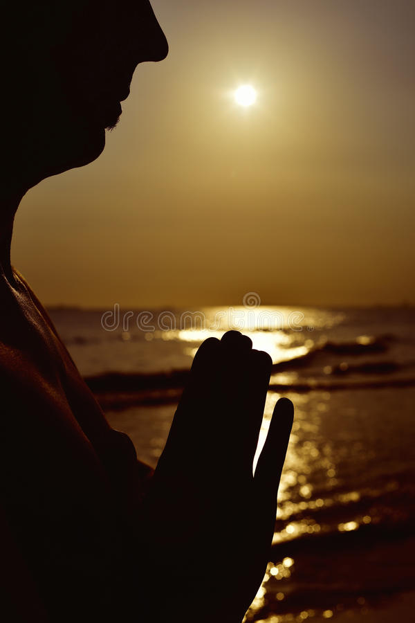 Man with his hands put together. The silhouette of a young man with his hands put together as prying in front of the sea in backlight stock images