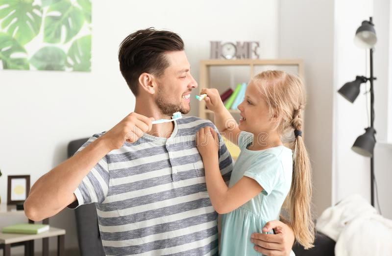 Man and his little daughter brushing teeth at home stock photos