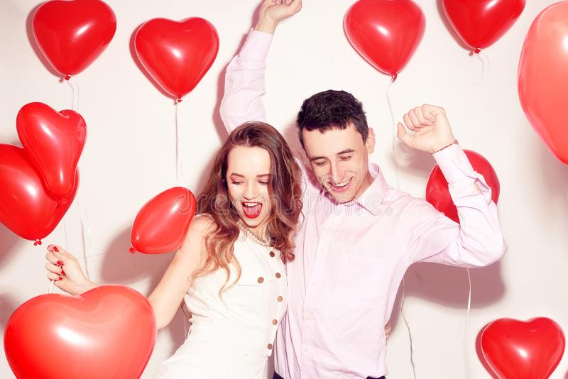 Man with his lovely sweetheart girl dance and have fun at Lover`s valentine day. Valentine Couple. Couple very happy, party time. Smile, laugh. Background red stock photos