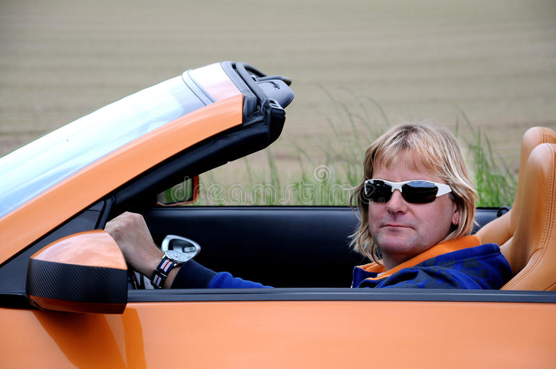 Man and his roadster. Blond sportive man with sunglasses riding his roadster royalty free stock image