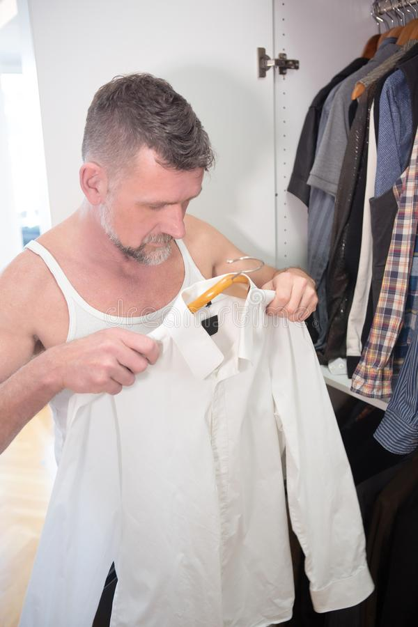 Man in his 50s getting dressed in front of closet. Handsome man in his 50s getting dressed in front of closet stock photos