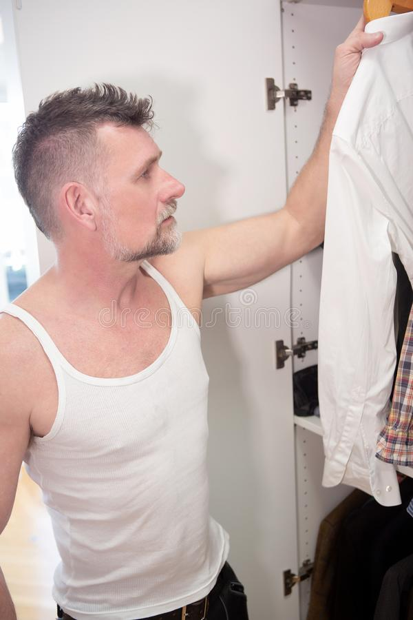Man in his 50s getting dressed in front of closet. Handsome man in his 50s getting dressed in front of closet royalty free stock photography