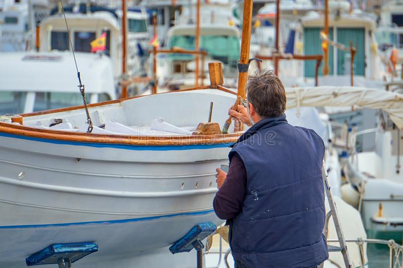 Man in His 50s or 60s Probably Retired Painting a Traditional Majorcan Boat.  royalty free stock photo
