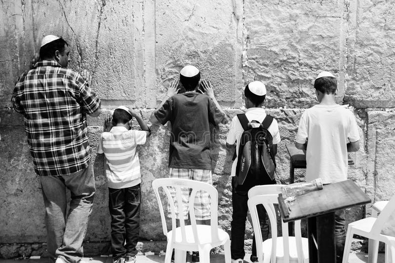 Man and his sons praying at the wailing wall, in black and white royalty free stock photo
