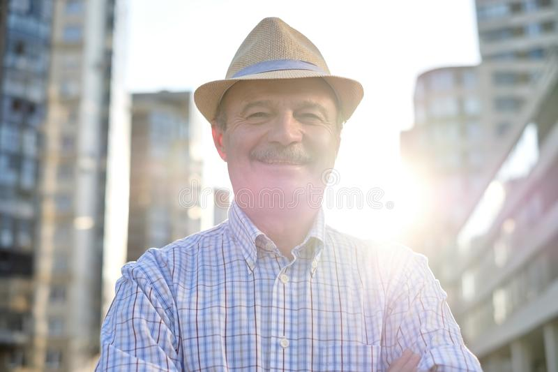 Man in hispanic hat with mustache looking at camera smiling in city. Senior hispanic man in hispanic hat with mustache looking at camera smiling in city centre stock image