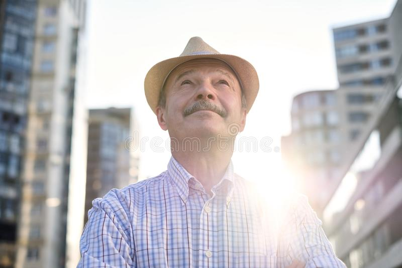 Man in hispanic hat with mustache looking at camera smiling in city. Senior hispanic man in hispanic hat with mustache looking at camera smiling in city centre royalty free stock photography