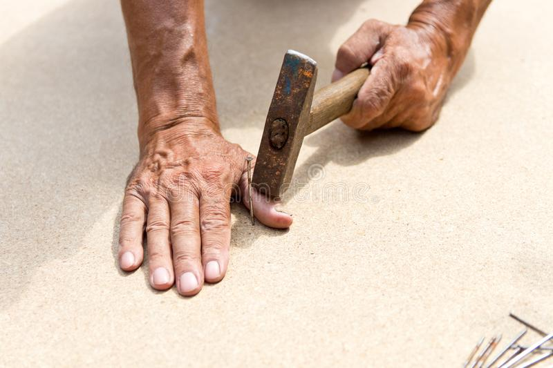 The man hit his finger with a hammer. Professional carpentry, woodwork and people. concept of injury in the workplace. Copy space. Board, injuries, thumb royalty free stock photos