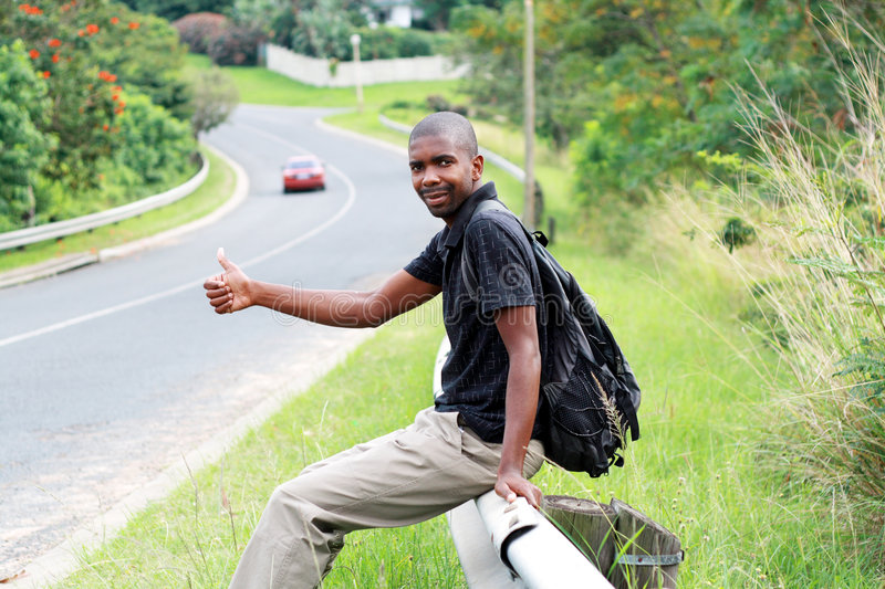 Man hitchhiking. A african backpacker sitting on roadside guardrail hitchhiking stock photography