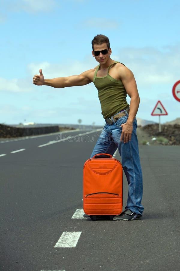 Man hitchhiking. Man on the road hitchhiking under with orange bag stock photo