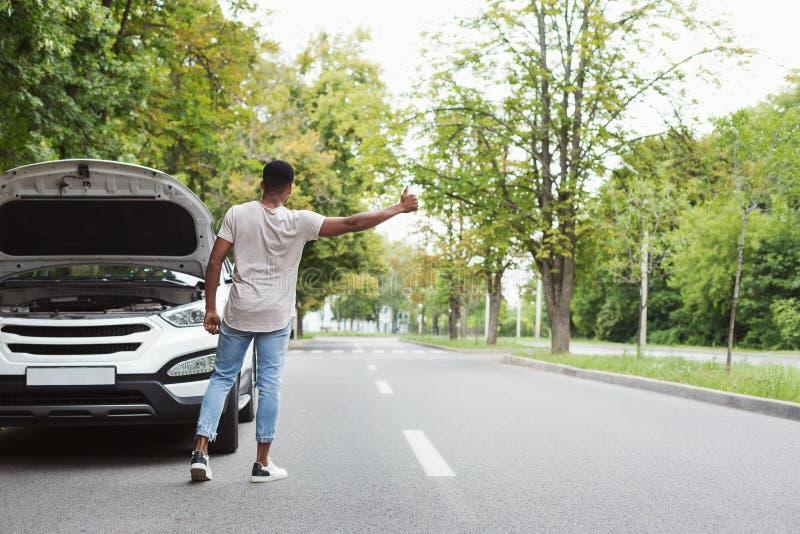 Man hitchhiking by broken car royalty free stock photo