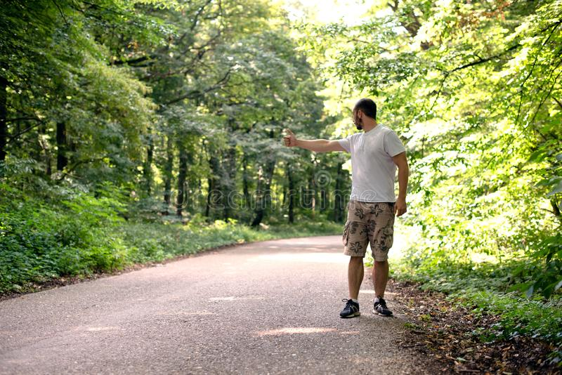 Man is hitchhiking stock photo