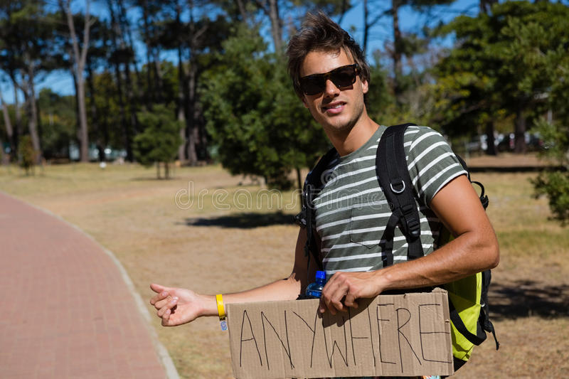 Man hitchhiking at roadside. On a sunny day royalty free stock photography