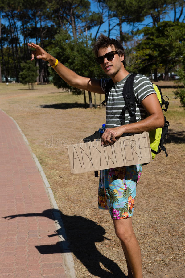 Man hitchhiking at roadside. On a sunny day royalty free stock photos