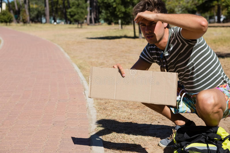 Man hitchhiking at roadside. On a sunny day stock photo