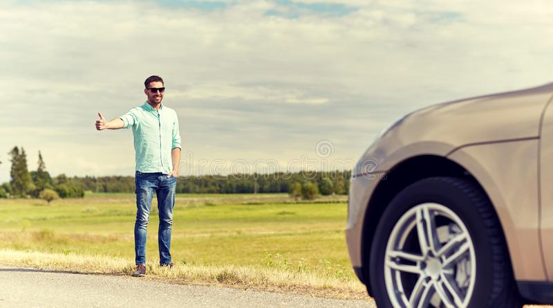 Man hitchhiking and stopping car at countryside. Road trip, hitchhike, travel, gesture and people concept - man hitchhiking and stopping car with thumbs up royalty free stock image