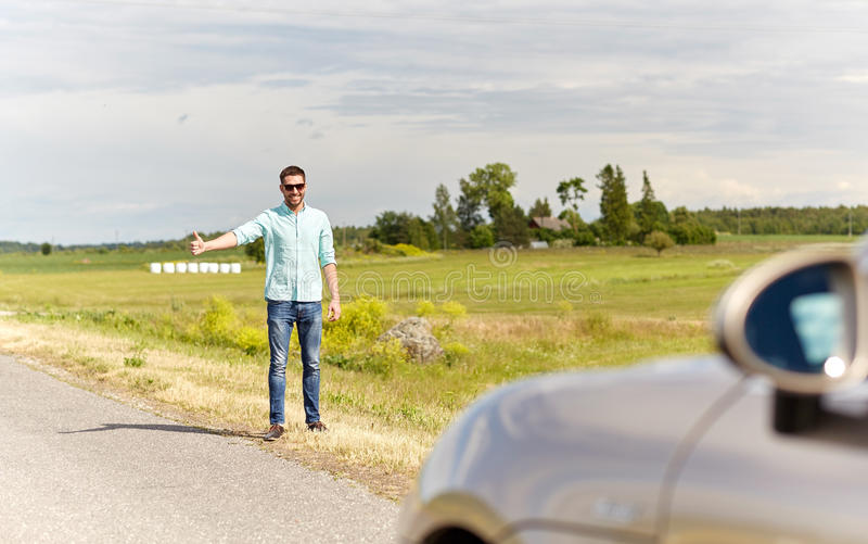 Man hitchhiking and stopping car at countryside. Road trip, hitchhike, travel, gesture and people concept - man hitchhiking and stopping car with thumbs up royalty free stock photography