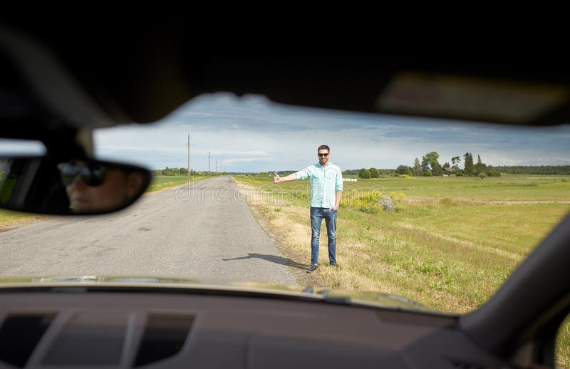 Man hitchhiking and stopping car with thumbs up. Road trip, travel, gesture and people concept - man hitchhiking and stopping car with thumbs up gesture at stock photo