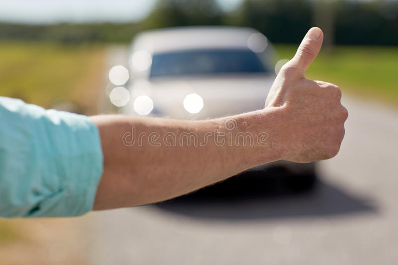 Man hitchhiking and stopping car with thumbs up. Road trip, travel, gesture and people concept - man hitchhiking and stopping car with thumbs up gesture at royalty free stock images