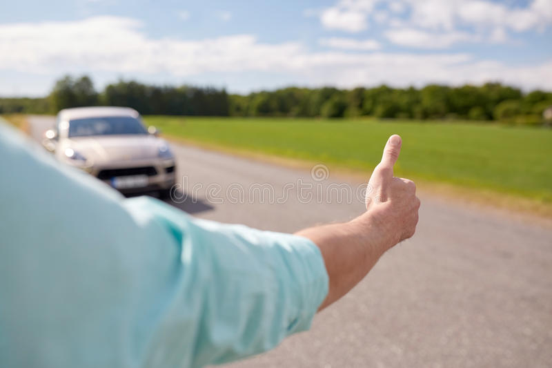 Man hitchhiking and stopping car with thumbs up. Road trip, travel, gesture and people concept - man hitchhiking and stopping car with thumbs up gesture at royalty free stock photography
