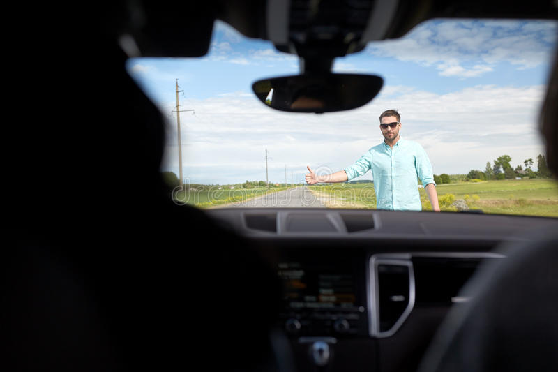 Man hitchhiking and stopping car with thumbs up. Road trip, travel, gesture and people concept - man hitchhiking and stopping car with thumbs up gesture at royalty free stock photos