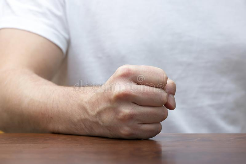 Man is hitting fist on the table. stock image