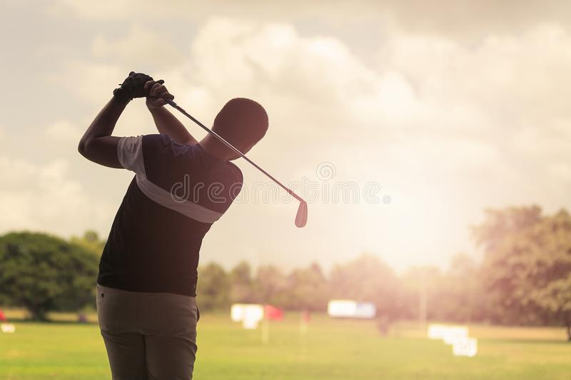 Man hitting golf shot with club on course at evening time. royalty free stock photos
