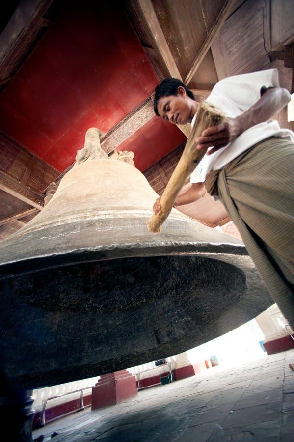 Man hitting the Mingun bell in Myanmar. Man hitting Mingun Bell is the largest ringing Bell in the World,located at Mingun temple,Sagaint Region in Myanmar royalty free stock photography