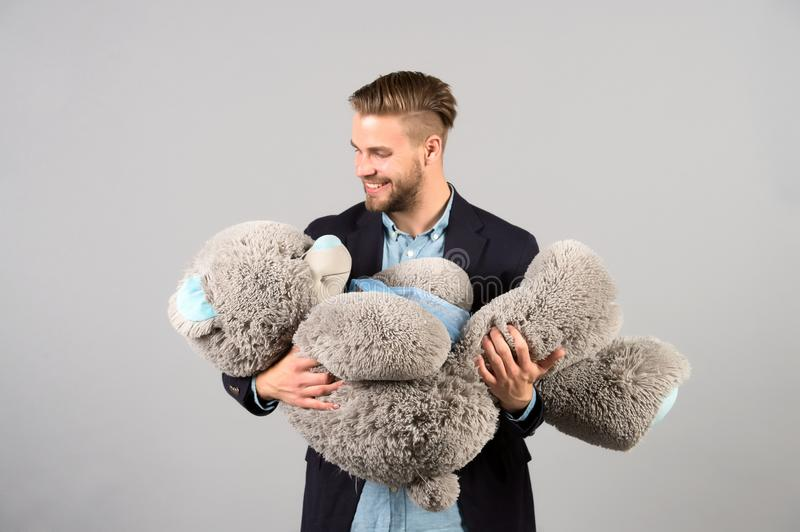 Man hold big teddy bear soft toy as present. For birthday party on grey background. valentines day stock photo
