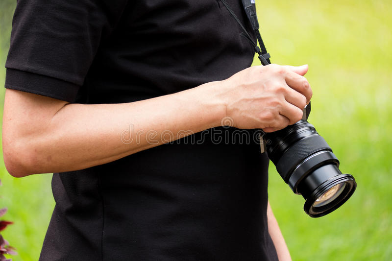 The man hold a black camera. By his right hand stock image