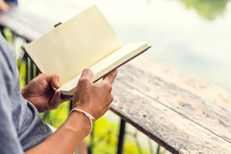 A man hold book and reading in the parks near the river. Man hold book and reading in the parks near the river royalty free stock photo