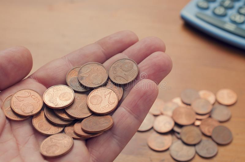 A man hold a buch of two euro cent coins in the palm of his hand over a table with other coins and a calculator stock photo
