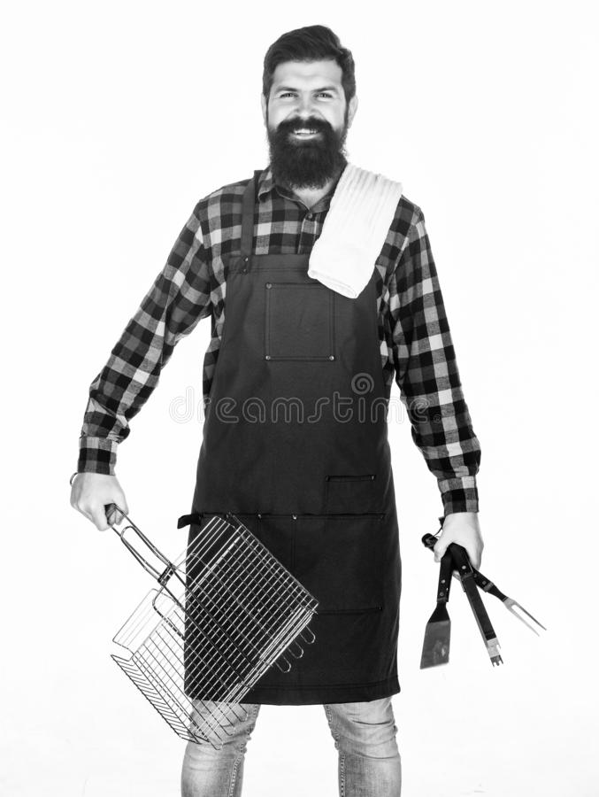 Man hold cooking utensils barbecue. Tools for roasting meat outdoors. Picnic and barbecue. Tips for cooking meat. Barbecue season. Bearded hipster wear apron royalty free stock photos