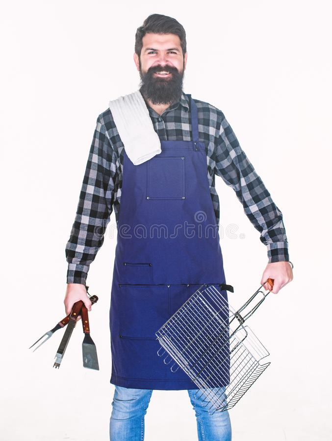 Man hold cooking utensils barbecue. Tools for roasting meat outdoors. Picnic and barbecue. Tips for cooking meat. Barbecue season. Bearded hipster wear apron royalty free stock photo