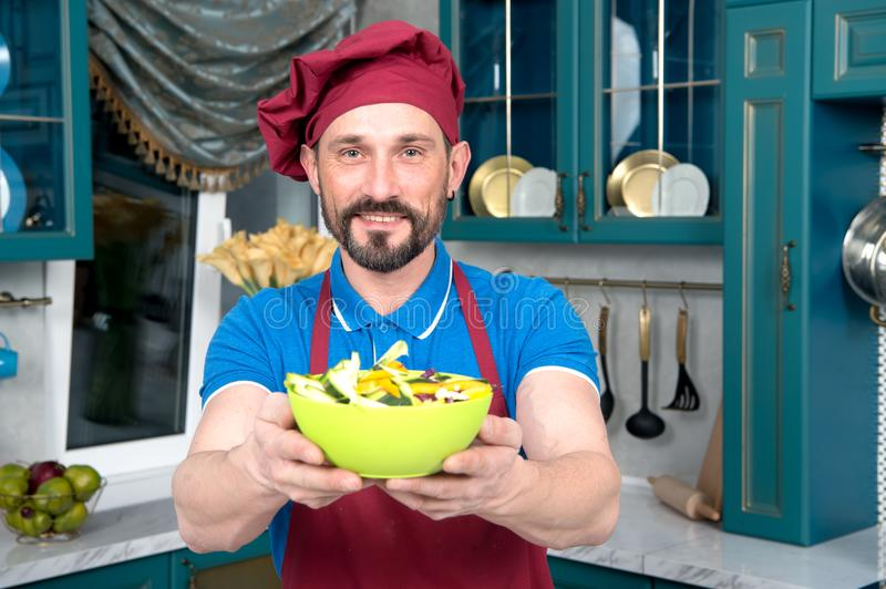 Man hold in hands fresh salad. Cheerful chef proposing salad. Smiled man cooked fresh vegetables at kitchen. Plate of salad in man hands. Cheerful chef royalty free stock photography