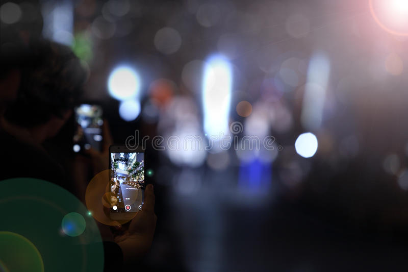 Man hold smart Phone and take photo vdo of pop star fashion show stock photography
